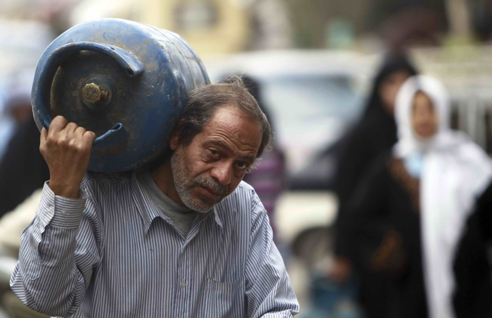 A man carries an empty gas cylinder on his back after the ones distributed by the army ran out in Cairo