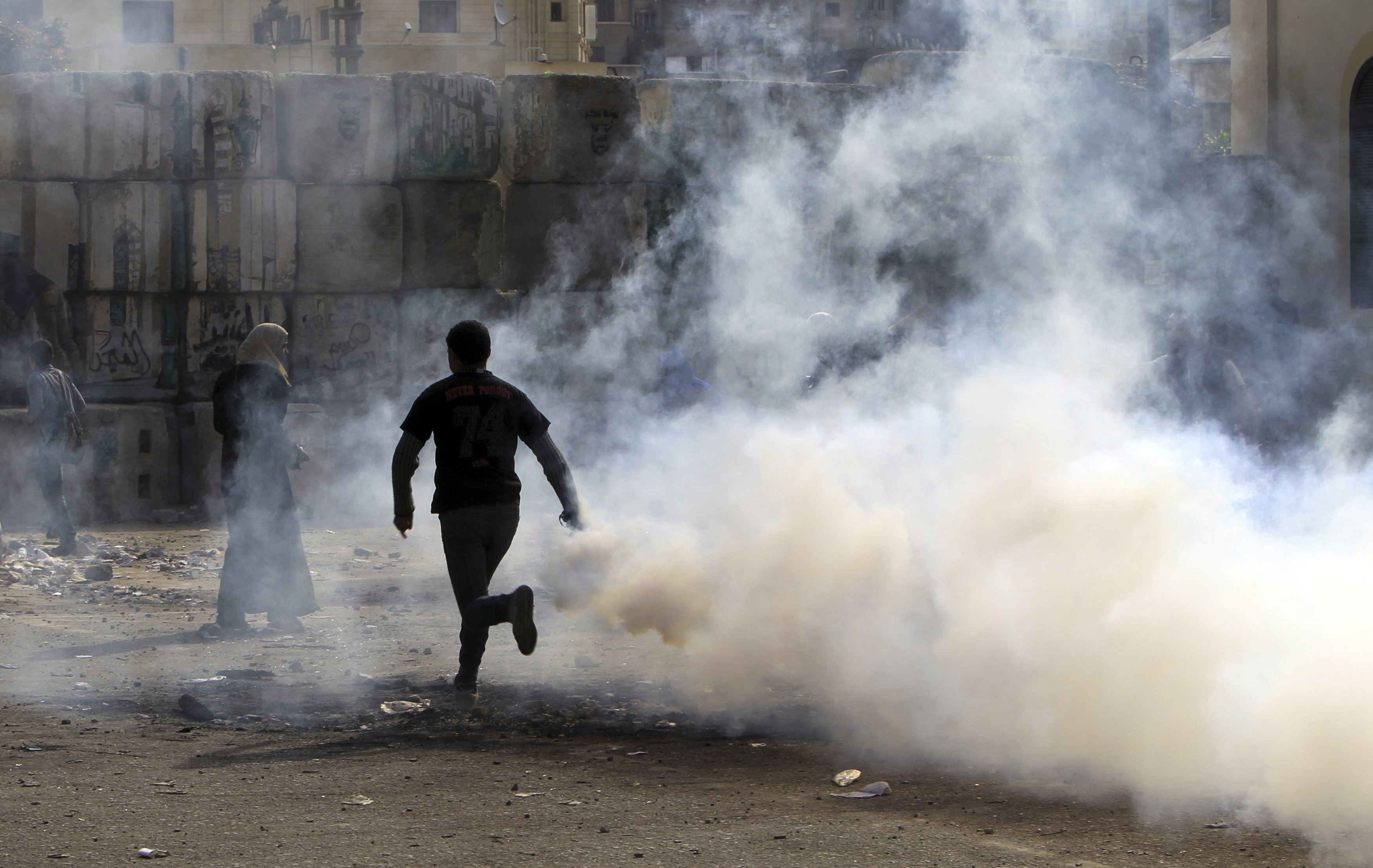 Protester runs with a tear gas canister, which was earlier fired by riot police, during a protest in Cairo