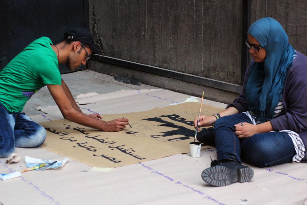 أحد افراد حمله مصريون ضد الفحم يرسمون لافته  تحمل شعار الحمله