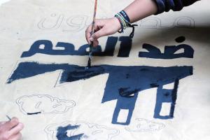 فتاة من حمله مصريون ضد الفحم ترسم شعار الحمله