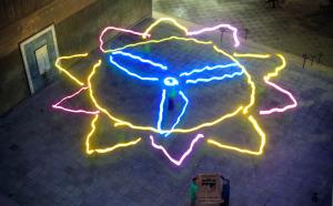 الصوره النهائيه للعمل الفني وهو عباره عن رسم بالضوء للشمس تتوسطها مروحة هوائيه لتوليد الطاقه