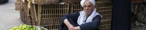 بائع ليمون عجوز يجلس في سوق شعبي