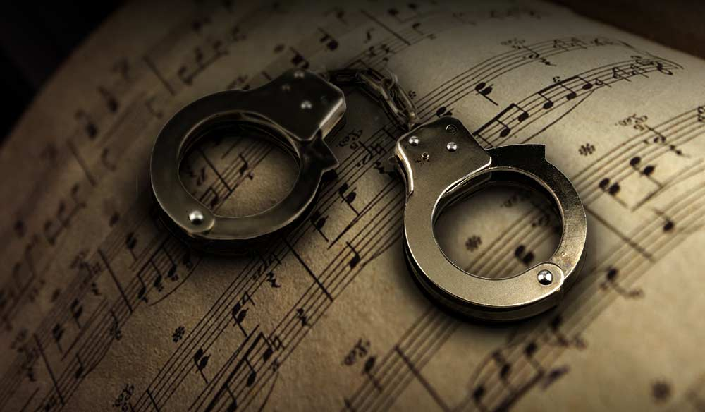 music notation sheet with handcuffs laying on top of it